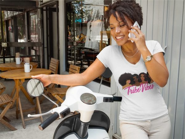 t shirt mockup of a woman leaning on her motorcycle next to a cafe