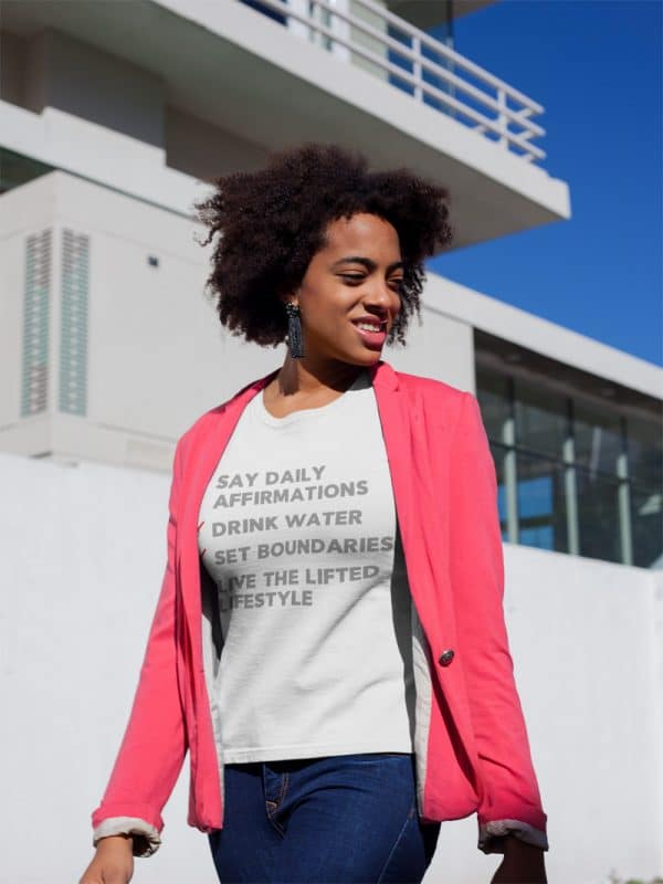 mockup of a woman wearing a t shirt and a sweet pink blazer outside a house